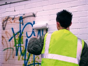 council worker removin graffiti from a wall