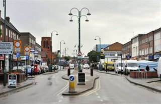 Shenley Road shopping parade in Borehamwood, looking west towards All Saints Church