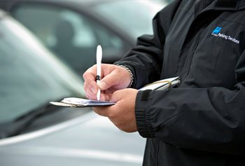 A close up photograph of a Civil enforcement officer writing a ticket