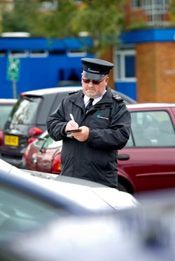 A photograph of a Civil enforcement officer writing a ticket
